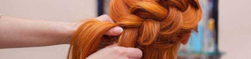 A close up of a person getting their hair braided.