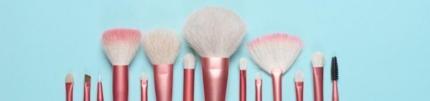 Pink makeup brushes in the skyblue background